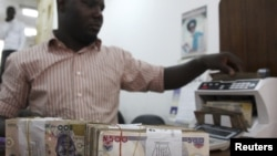 A money dealer counts the Nigerian Naira on a machine in his office in the commercial capital of Lagos, Nigeria.