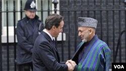 Presiden Hamid Karzai (kanan) disambut oleh PM David Cameron saat tiba di kantor PM Inggris di London (1/3).