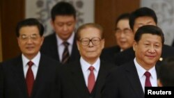 China's President Xi Jinping (R) walks with retired leaders Jiang Zemin (C) and Hu Jintao (L) as they arrive at the National Day Reception to mark the 65th anniversary of the founding of People's Republic of China, at the Great Hall of the People, in Beij