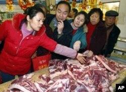 ລູກຄ້າຊື້ຊີ້ນໝູ ຢູ່ຕະຫລາດແຫ່ງນຶ່ງໃນແຂວງ Sichuan ປະເທດຈີນ.