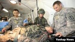 16일 서울 특수전사령부에서 열린 사상 첫 한·미 연합 군종 야외기동훈련에 참가한 군종장교가 야전수술시 군종조치훈련에서 부상자 머리에 손을 올리고 기도하고 있다.