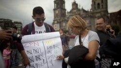 Jóvenes mexicanos muestran en el Zócalo de la capital un cartel con la puntuación de los candidatos presidenciales, según sondeos.