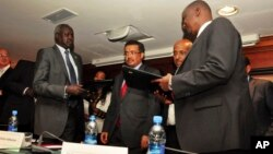 Nhial Deng Nhial (left) of South Sudan's negotiating team and Taban Deng Gai (right), negotiator for Riek Machar's rebel group, exchanged signed cessation of hostilities agreements in Addis Ababa one year ago, but South Sudan is still mired in conflict.