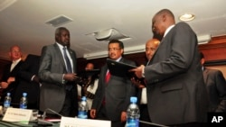 Nhail Deng Nhail, 2nd from left, the head of South Sudan's negotiating team, and lead negotiator for the rebels, Taban Deng Gai, right, sign a ceasefire agreement in front of Ethiopia's foreign minister, Tedros Adhanom.