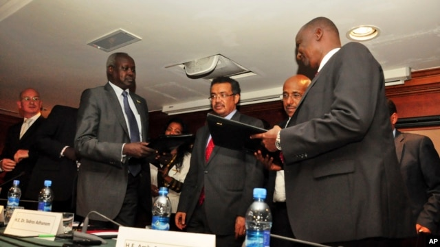 Nhail Deng Nhail, 2nd left, the head of South Sudan's negotiating team, and top negotiator for the rebel's side, Taban Deng Gai, right, a general in South Sudan's army before he defected, sign a cessation of hostilities agreement in Addis Ababa, Jan 23, 2014.