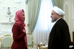 In this photo released by the official website of the office of the Iranian Presidency, Iran's President Hassan Rouhani, right, greets European Union foreign policy chief Federica Mogherini at the president's office in Tehran, Iran, July 28, 2015.