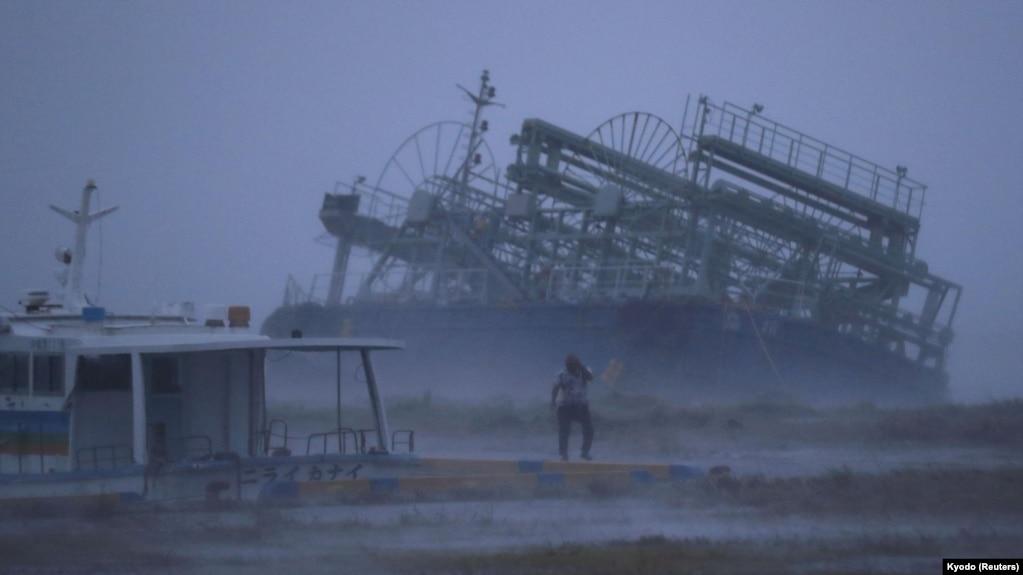 Un barco arrastrado por el tifón Trami en la orilla de en un puerto de Yonabaru, mientras una persona camina en medio de la tormenta en la isla sureña de Okinawa, Japón, el 29 de septiembre de 2018.