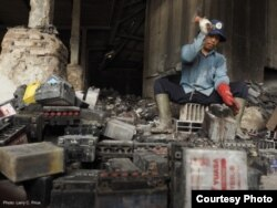 A man in Tegal, Indonesia, uses a hammer to break up old batteries by hand. Credit: LarryC. Price
