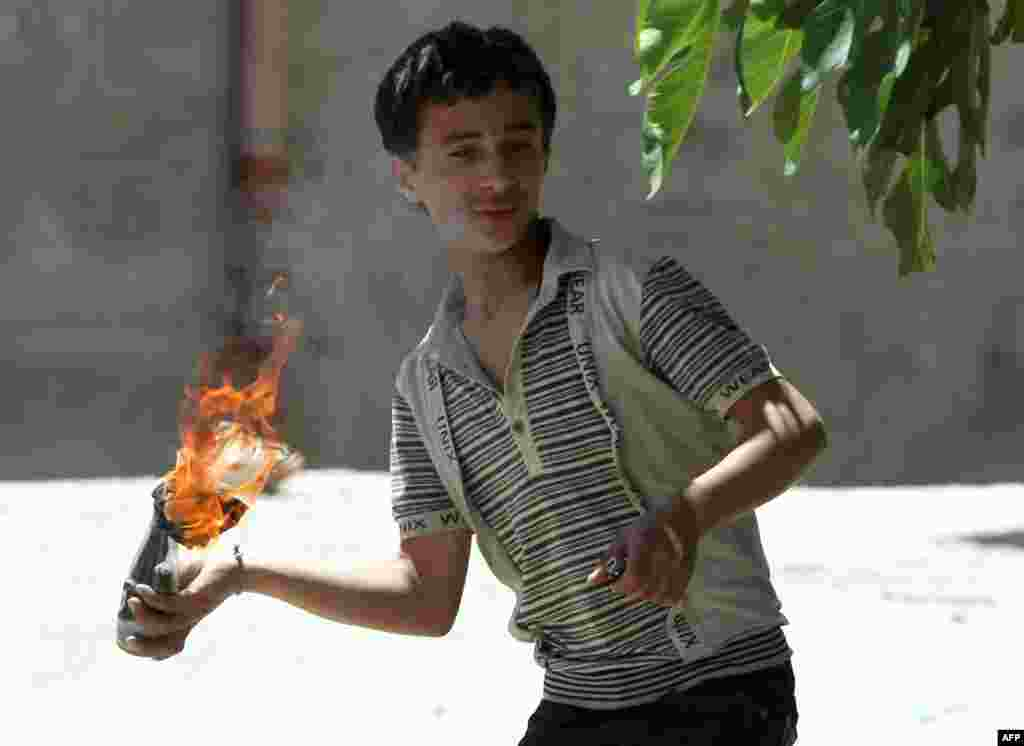 A Palestinian boy readies to throw a flaming molotov cocktail towards Israeli soldiers deployed at the entrance of the al-Aroub Palestinian refugee camp, May 15, 2012.