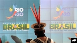 An Ashanink indigenous man stands before a poster promoting the launch of the Rio + 20 sustainable development conference in Brazil