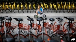 FILE - A child rides past bicycles from bike-sharing companies parked along a sidewalk in Beijing, Aug. 31, 2017. A report says China's factory activity expanded in September at the fastest pace in five years, indicating a healthy outlook for the world's