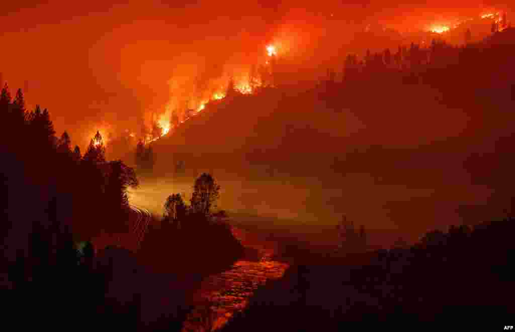 Light from a train is seen near the Sacramento River as flames from the Delta Fire fill a valley in Delta, California.