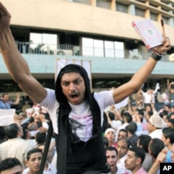 "A man carries a Koran and a cross during a demonstration by Egyptian Christians and Muslims shouting ""Muslims and Christians hand in hand"" in front of the Egyptian Television building in downtown Cairo, May 8, 2011"