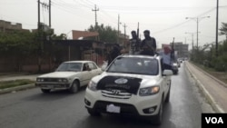 ພວກນັກລົບອິສລາມ ອີຣັກ ແລະ Levant (ISIL) ພາກັນສະຫລອງ ດ້ວຍຍຶດເອົາລົດ ກຳລັງຮັກສາຄວາມປອດໄພ ລັດຖະບານອີຣັກ.