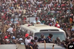 Nigerian presidential candidate Muhammadu Buhari, center, from the All Progressives Congress (APC) party rides atop a bus as he arrives for a party rally in Kano, Jan. 20, 2015.