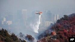 소방 헬기가 로스앤젤레스 인근에 발생한 산불을 진압하기 위해 물을 뿌리고 있다.