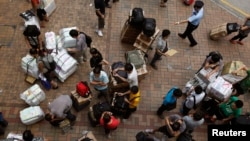A policeman (top, R) asks mainland Chinese visitors to unblock a pavement outside Hong Kong's Sheung Shui train station, Aug. 23, 2012.
