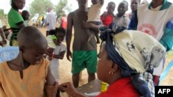 FILE - A child receives a measles vaccine in a camp set up by the UNHCR in Nangungue, Cameroon, April 12, 2013.