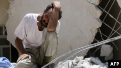 A man looks on as Syrian civil defense workers (not pictured) look for survivors under the rubble of a collapsed building following reported airstrikes July 17, 2016, in the rebel-controlled neighborhood of Karm Homad in the northern city of Aleppo.