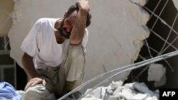 Un homme cherche des survivants après l'effondrement d'un bâtiment au nord de la ville d'Alep, Syrie, le 17 juillet 2016.