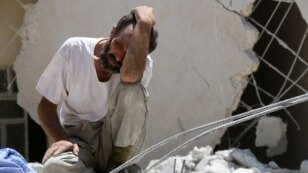 FILE - A man looks on as Syrian civil defense workers look for survivors under the rubble of a collapsed building following reported airstrikes in the rebel-controlled neighborhood of Karm Homad in Aleppo, July 17, 2016.