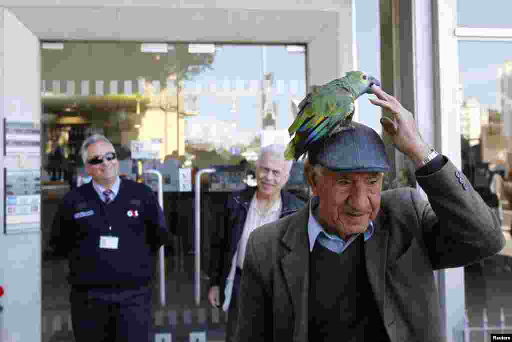 A man walks with a parrot on his hat in front of a Bank of Cyprus branch before it opens in Nicosia, March 28, 2013.