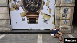 """Un desamparado con un letrero de """"tengo hambre"""" en una calle de la ciudad de Salónica, en Grecia."""