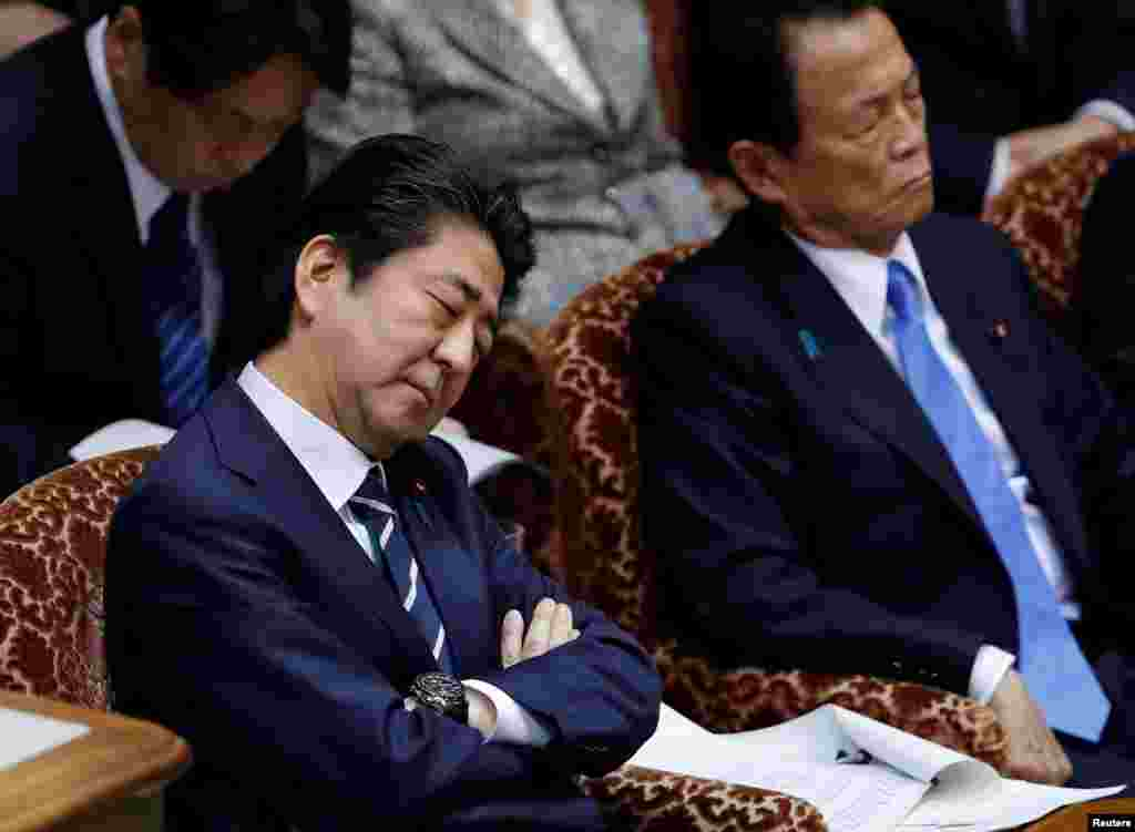 Japan's Prime Minister Shinzo Abe and Finance Minister Taro Aso attend an upper house parliamentary session in Tokyo.