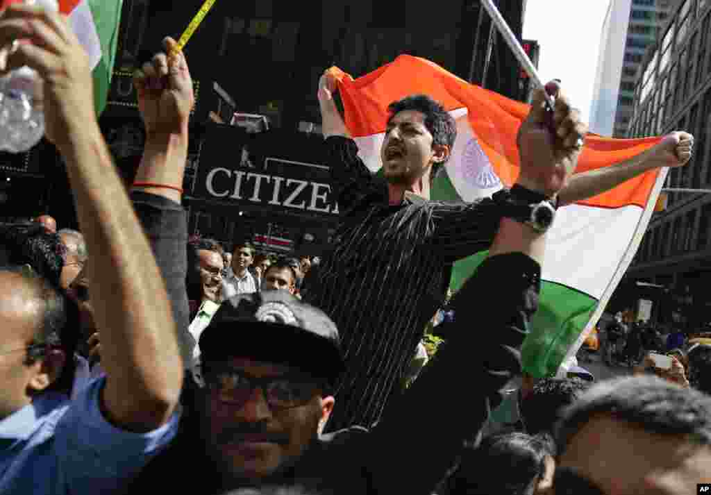 Supporters of Indian Prime Minister Narendra Modi shout slogans as they watch a live stream of Modi's speech from Madison Square Garden, in Times Square, New York, Sept. 28, 2014.