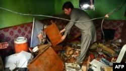 Một người dân Pakistan đang xem các vật dụng bị hư hại sau vụ nổ bom ở Karachi, 15/3/13