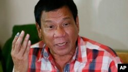 FILE - Presumed Philippine president-elect Rodrigo Duterte gestures during a news conference.