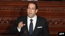 FILE - Tunisian Prime Minister Youssef Chahed addresses the parliament in Tunis on the country's anti-corruption fight, July 20, 2017.
