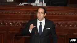 FILE - Tunisian Prime Minister Youssef Chahed addresses the parliament on the country's anti-corruption fight on July 20, 2017, in Tunis.