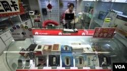 Toko di Beijing menjajakan produk-produk ponsel pabrik Huawei yang juga menjadi andalan ekspor Tiongkok (foto: dok). Surplus perdagangan TIongkok menurun seiring berkurangnya permintaan barang ke Eropa dan Amerika.