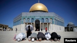 Palestinians pray in front of the Dome of the Rock at the compound known to Muslims as Noble Sanctuary and to Jews as Temple Mount in Jerusalem's Old City, Oct. 5, 2014.