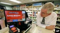 Un gerente de una tienda de conveniencia observa el monitor que anuncia el premio de Powerball.