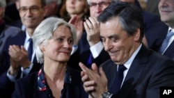 Conservative presidential candidate Francois Fillon applauds while his wife, Penelope, looks on as they attend a campaign meeting in Paris, Jan. 29, 2017. Financial prosecutors are investigating whether the former prime minister's wife was paid for work she didn't do.