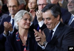 FILE - Conservative presidential candidate Francois Fillon applauds while his wife, Penelope, looks on as they attend a campaign meeting in Paris, Jan. 29, 2017.