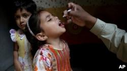 ARSIP - Seorang pekerja kesehatan memberikan vaksin polio ke seorang anak perempuan di Lahore, Pakistan, Senin, 9 April 2018 (foto: AP Photo/K.M. Chaudary)