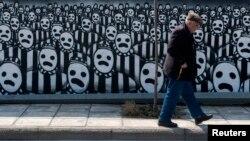مردی ازبرابر دیوارنگاری که به قربانیان هولوکاست تقدیم شده می گذرد. تسبلونیکی، یونان. ۱۵ مارس ۲۰۱۵