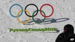 Seorang pria berjalan melewati gelang-gelang Olimpiade dengan tulisan Olimpiade Musim Dingin Pyeongchang 2018, di Pyeongchang, Korea Selatan, 3 Februari 2017.