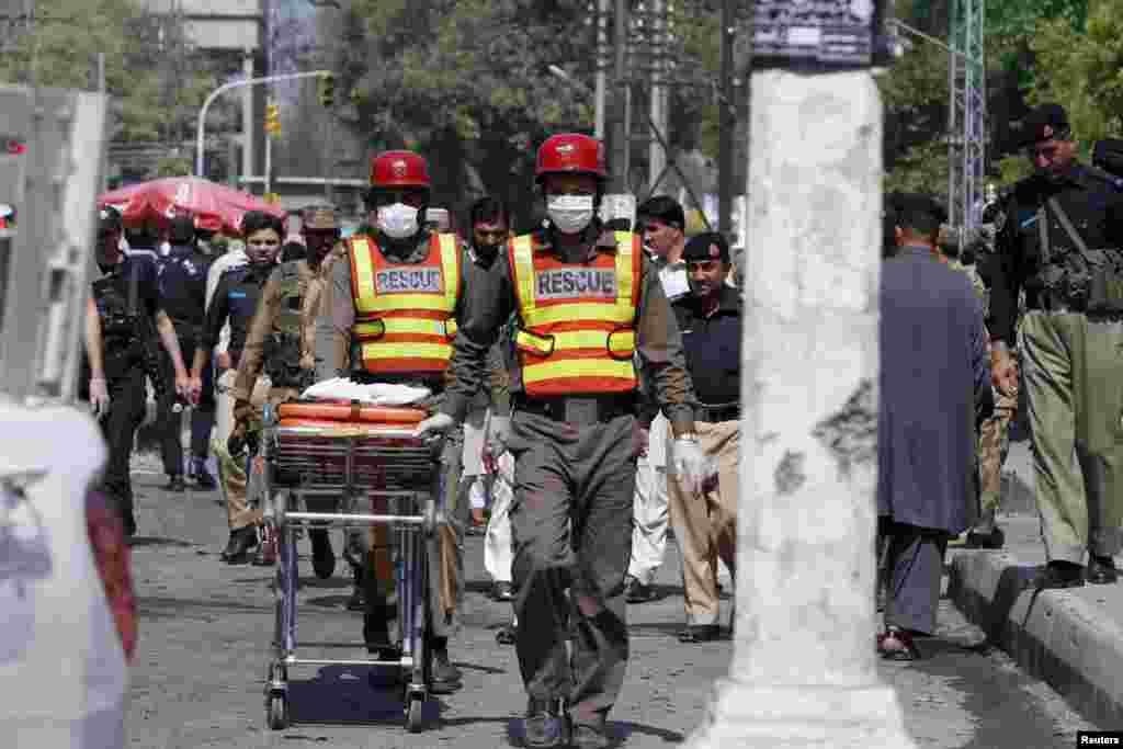 Rescue workers transport body parts of blast victims from the site of a bomb attack in Peshawar, Pakistan, March 29, 2013.