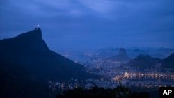 FILE - The Christ the Redeemer statue stands atop the Corcovado Mountain, left, at dawn in Rio de Janeiro, Brazil, July 29, 2016.