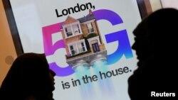 Dua warga Inggris melewati iklan jaringan 5G di sebuah toko ponsel di London (foto: ilustrasi).