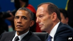 U.S. President Barack Obama listens as Australian Prime Minister Tony Abbott makes opening remarks at the first plenary session of the G20 Summit in Brisbane, Australia Saturday, Nov. 15, 2014.