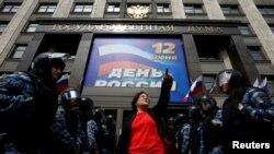 Aktivis Yulia Galyamina dikelilingi oleh polisi yang sedang bertugas, saat melakukan aksi unjuk rasa di depan Duma Negara Bagian, majelis rendah parlemen, di Moskow, Rusia, 9 Juni 2017, memprotes rencana kontroversial untuk meruntuhkan apartemen bertingkat era Soviet. (REUTERS/Sergei Karpukhin).
