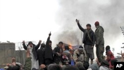 Afghan men shout anti-U.S slogans during a protest outside the U.S. military base in Baghram, north of Kabul February 21, 2012.