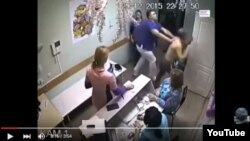 This image, taken from YouTube, shows the Russian physician shoving the patient through a doorway.