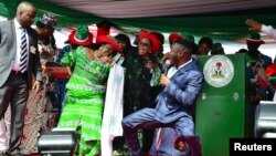 Patience Jonathan (C), wife of Nigeria's President Goodluck Jonathan, dances with supporters during a rally by Jonathan's ruling People's Democratic Party, March 14, 2015.