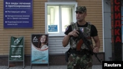 An armed serviceman stands guard at a cordon near a cafe, where leader of the separatist self-proclaimed Donetsk People's Republic Alexander Zakharchenko was killed, in Donetsk, Ukraine, Aug. 31, 2018.